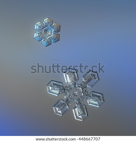 Two snowflakes, sparkling on smooth gray/blue gradient background. This is real snow crystals (around one and three millimeters in size), captured on glass surface with multi-color LED back light. - stock photo