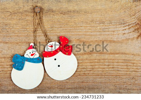 Two snowman hanging on nail on old wooden background - stock photo
