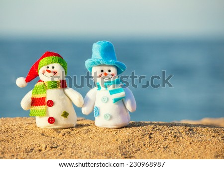 Two snowman on sand near sea. Christmas decoration. Vacations - stock photo