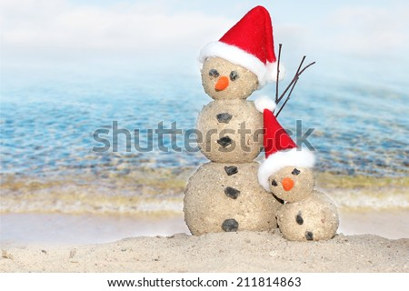 Two Snowmen at sea beach in santa hats - stock photo