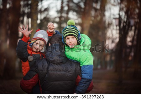 Two sons and his father, outdoor portrait. Father holding two sons. fun, joy, happiness, friendship. - stock photo