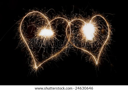 Two sparkling hearts isolated on black - stock photo