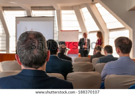 two speakers and people sitting rear at the business conference - stock photo
