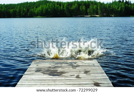Two splashes left by people who dived from the pier on the lake - stock photo