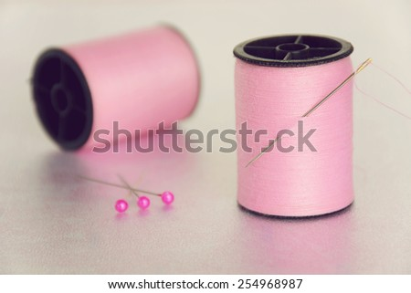 Two spools of pink thread with one with a needle stuck in it. /Sewing Concept - stock photo