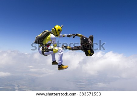 Two sports parachutist build a figure in free fall. - stock photo