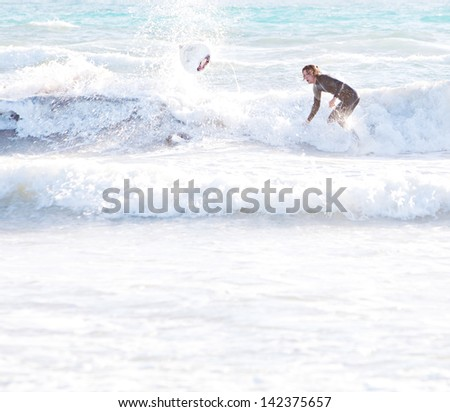 Two sports surfer men starting to ride a wave, one standing up on his board and the other falling down into the sea, leaving a flying surfing board and splashing water during a summer day on vacation. - stock photo