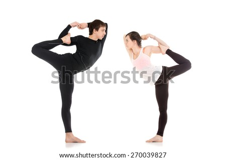 Two sporty people practice yoga in pair, fit couple doing acroyoga, stretching exercise, asana Maha Natarajasana, king dancer (Lord of the Dance) pose, balance workout - stock photo