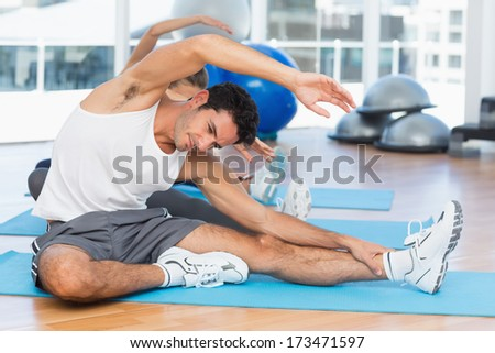 Two sporty people stretching hands at yoga class in fitness studio - stock photo