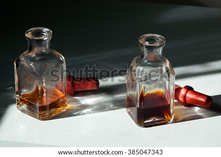 Two square apothecary eye dropper bottles with brown essential oils on white shelf in sunlight. - stock photo