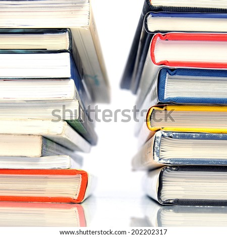 Two stacks of multicolored books on white background - stock photo
