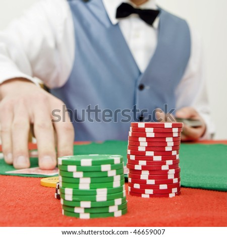 Two stacks of poker chips on a table with a game in progress, dealer dealing cards (selective focus on the chips) - stock photo