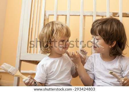 Two stained child with brushes home - stock photo