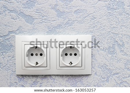 Two standard sockets on blue wall - stock photo