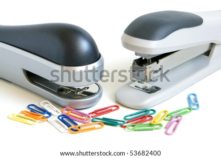 Two staplers and multicolored paper clips on a white background - stock photo