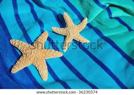 two starfish / seastars on striped beach towel - stock photo