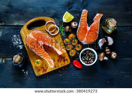 Two steaks of salmon with fresh ingredients for tasty cooking on rustic wooden background, top view, banner. Healthy food concept. - stock photo
