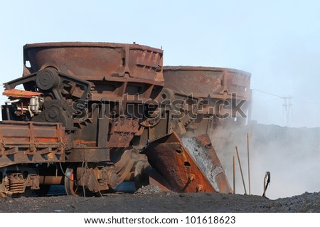 Two steel buckets to transport the molten metal, mounted on railway platforms. - stock photo