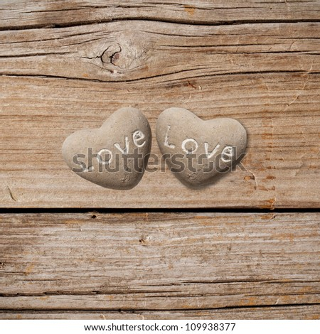 Two stone hearts on rustic wood - stock photo