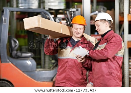 two store workers man in uniform in front of warehouse forklift loader discussing order - stock photo