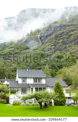 Two- storied cottages in mountains, waterfall and mist. - stock photo