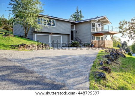 Two story house exterior with gray siding and concrete driveway. And natural stone landscape design. - stock photo