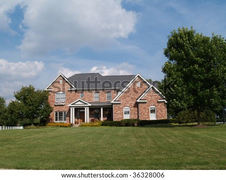 Two story large brick residential home with flower box. - stock photo