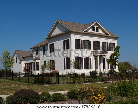 Two story new home built to look like an old historical home complete with the added on look, painted brick and a wrought  iron fence. - stock photo