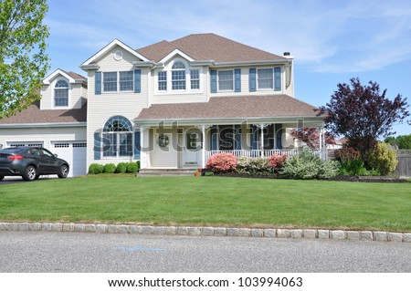 Two Story Suburban Home Landscaped with Pink Azaleas Japanese Maple Front Lawn Grass Curb - stock photo