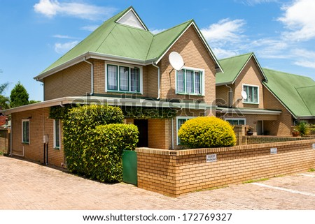 Two story town house with green roof and guest parking lot. - stock photo