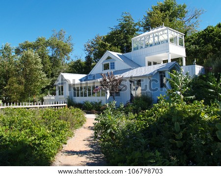 Two story white cottage on the beach at the end of a sandy path. - stock photo
