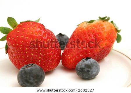 Two strawberries & blueberries upclose - stock photo