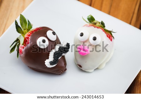 two strawberries on a white plate dipped in chocolate and decorated for a romantic concept - stock photo