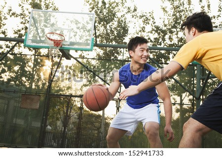 Two street basketball players on the basketball court - stock photo