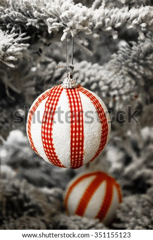 Two striped balls hanging on Christmas tree covered with snow. Vintage Christmas card. Selective focus. Toned photo. - stock photo