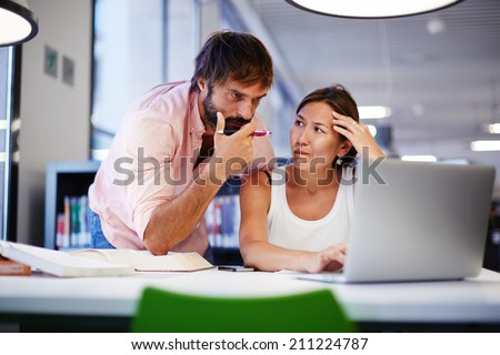 Two student friends working with laptop in library, couple at exam preparation working together, students learning in library with computer, teenagers surfing the net - stock photo
