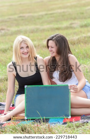 Two student girls holding board for writing - stock photo