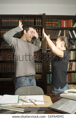 Two students giving celebrating joyfully in office surrounded by paperwork. Vertically framed photo. - stock photo