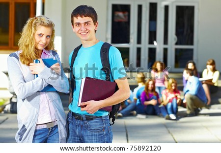 Two students in front of group of students near the university - stock photo