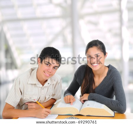 Two students in modern educational facility. Teenage boy and girl with books open on their desk. Square format. Back to school concept. - stock photo