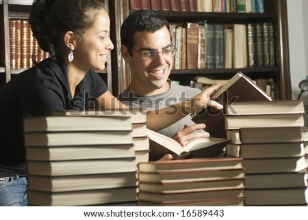 Two students looking at books in office. Horizontally framed photo. - stock photo