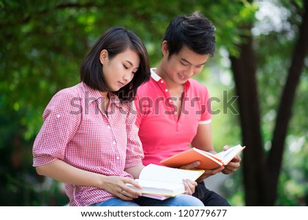 Two students reading for seminar outdoors - stock photo