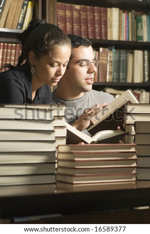 Two students reading next to a stack of books. Vertically framed photo. - stock photo