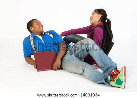 Two students seated on the floor looking at each other. They are smiling and laughing. They wear backpacks and he holds a notebook. Horizontally framed photograph. - stock photo