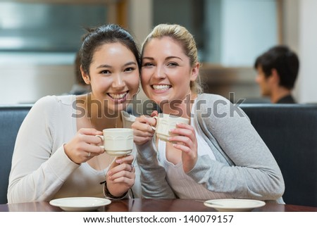Two students sitting in college coffee shop while drinking and holding a cup of coffee - stock photo