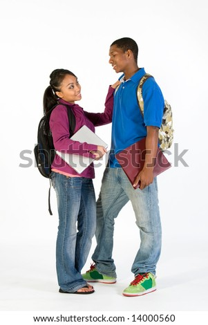 Two students stand and look at  each other with happy expressions on their faces. They wear backpacks and he carries a notebook. She has her arm on his shoulder. Vertically framed photograph. - stock photo