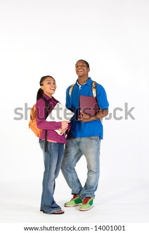 Two students stand and look at  the camera with happy expressions on their faces. They wear backpacks and he carries a notebook. Vertically framed photograph. - stock photo