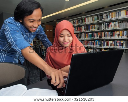 Two students studying together in a library. - stock photo