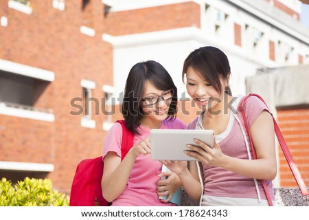 two students using a tablet to discuss homework - stock photo