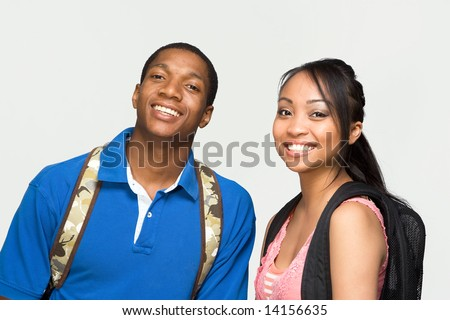 Two students wearing backpacks are laughing. Horizontally framed photograph - stock photo